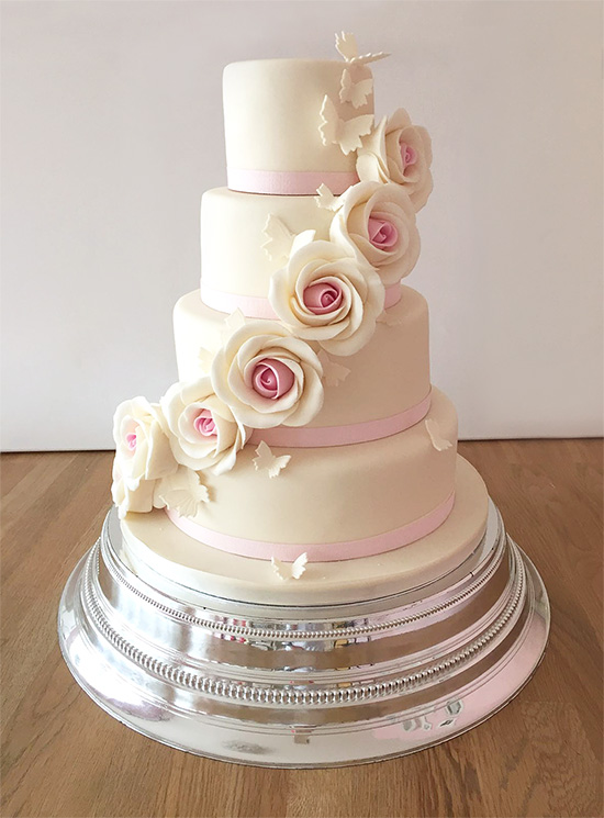 Ivory wedding cake with roses and butterflies